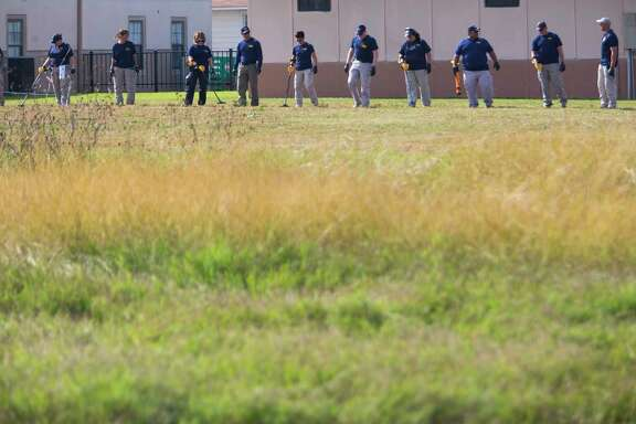 Law enforcement officials with the FBI sweep the grassy area next to the First Baptist Church of Sutherland Springs with metal detectors, Monday morning, Nov. 6, 2017, in Sutherland Springs.