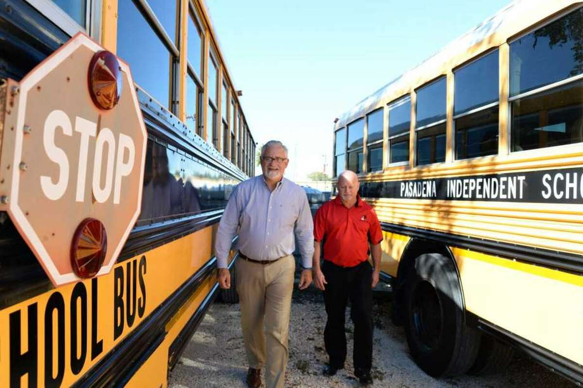 Keith Moore, director of transportation for Pasadena ISD, right, takes a walk with assistant director Jim Jacobs through one of the 'mud lots' at the district's transportation work yard on Lafferty. Included in the district's $135 million bond on the Nov 7 ballot is the rebuild of transportation facilities and purchase of new buses.