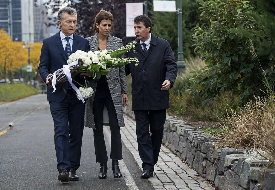 Argentine President Mauricio Macri (left) and his wife, Juliana Awada, place flowers at the scene in New York City where cyclists and pedestrians were killed in a terrorist attack. Photo: Craig Ruttle, Associated Press