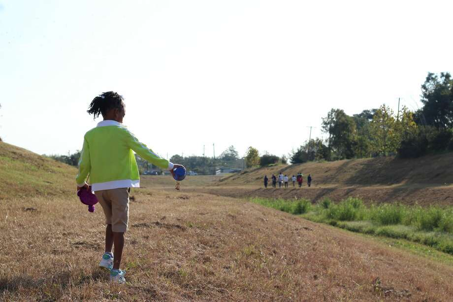 A girl spreads wildflowers seeds next to Sims Bayou.  Photo: Houston Parks Board