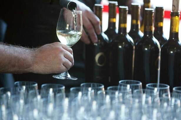 A glass of whit wine is poured at the Cynthia Woods Mitchell Pavilion Wine Dinner on Sunday.