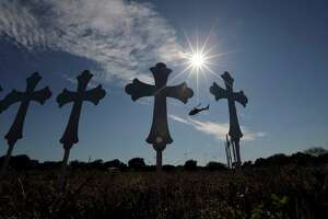 A law enforcement helicopter flies over crosses placed near the scene of a shooting at the First Baptist Church of Sutherland Springs, Monday, Nov. 6, 2017, in Sutherland Springs, Texas. A man opened fire inside the church in the small South Texas community on Sunday, killing and wounding many. (AP Photo/Eric Gay)