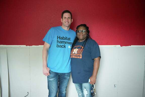 Tarek El Moussa (left) and Zipporah Smith (right) who's home was flooded during Hurricane Harvey gets repairs for her home from Habitat for Humanity Friday November 3, 2017.