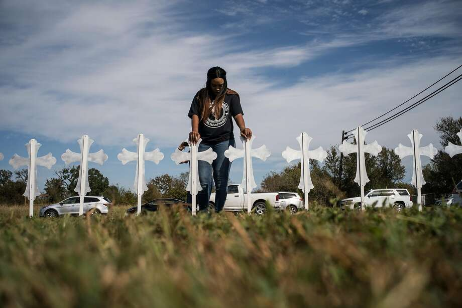 Sheree Rumph of San Antonio, prays over crosses that were put up outside a gas station in Sutherland Springs, Texas, where a gunman killed at least 26 people and injured at least 20 more during a late-morning church service a day earlier, Nov. 6, 2017. (Todd Heisler/The New York Times) Photo: TODD HEISLER, NYT