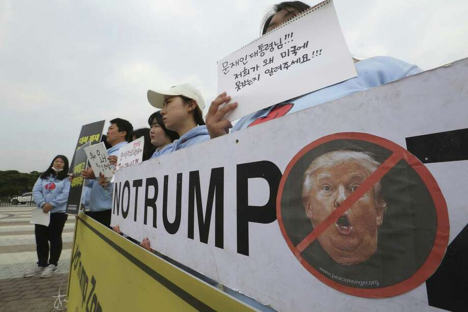 South Korean protesters stage a rally against a visit by the U.S. President Donald Trump, near the presidential Blue House in Seoul, South Korea. Readers weigh in on Trump. Photo: Ahn Young-joon /Associated Press / Yonhap