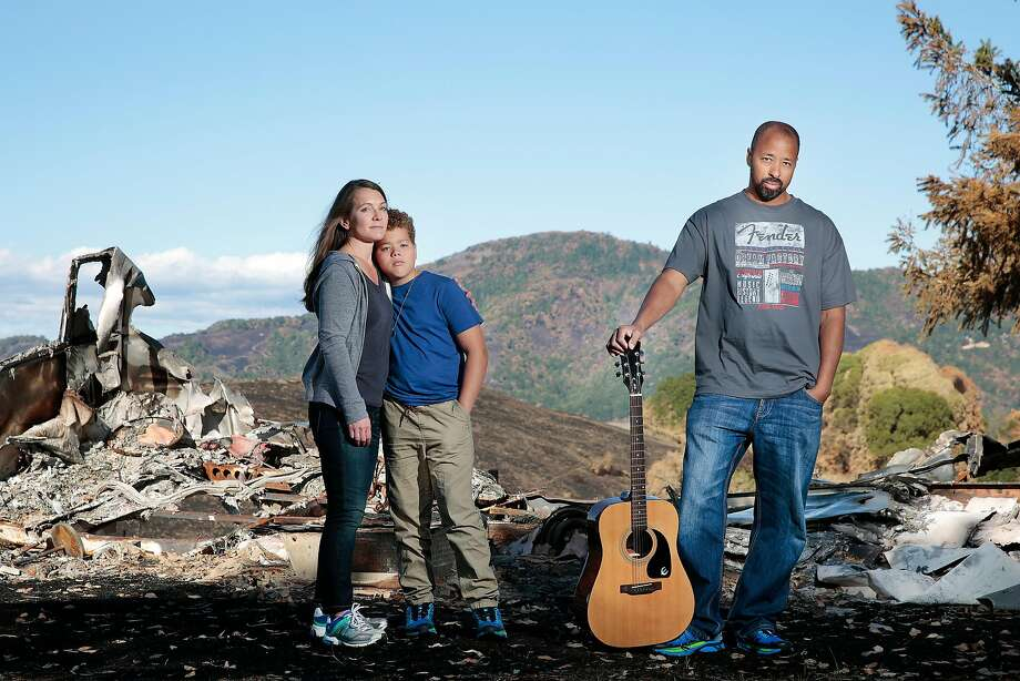 Debra, Isaac and Terry Sanders pose next to a burned trailer on the property of the insurance-provided home where they will live for a year in Santa Rosa. Terry lost his guitar collection along with his home. Photo: RAMIN RAHIMIAN, Special To The Chronicle