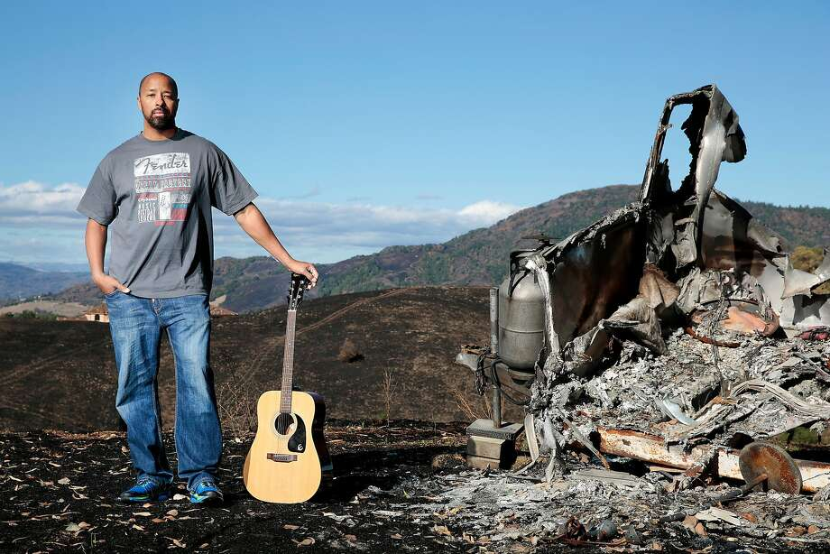 Terry Sanders, an Oakland firefighter, stands with his new guitar next to a burnt trailer on the property of the insurance-provided rental home his family will live in for a year in Santa Rosa. The Sanders family lost its Santa Rosa home in the Tubbs Fire. Photo: RAMIN RAHIMIAN, Special To The Chronicle