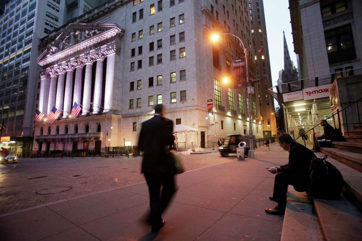 A man walks to work on Wall Street, near the New York Stock Exchange, in New York. The price of oil hit a two-year highon Nov. 6, 2017 after a spate of high-profile arrests in Saudi Arabia. (AP Photo/Mark Lennihan, File)