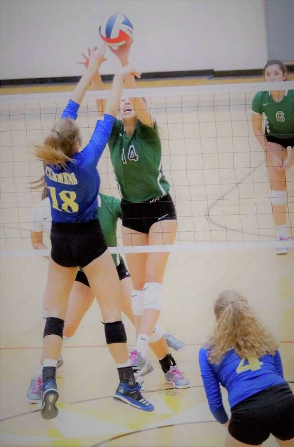 Clemens outside hitter Lauren Teske (18) and Reagan's Kaja Burja (14) battle at the net during second-game action in Reagan's 3-0 playoff win Nov. 3. Photo: Lavon Brown / Northeast Herald