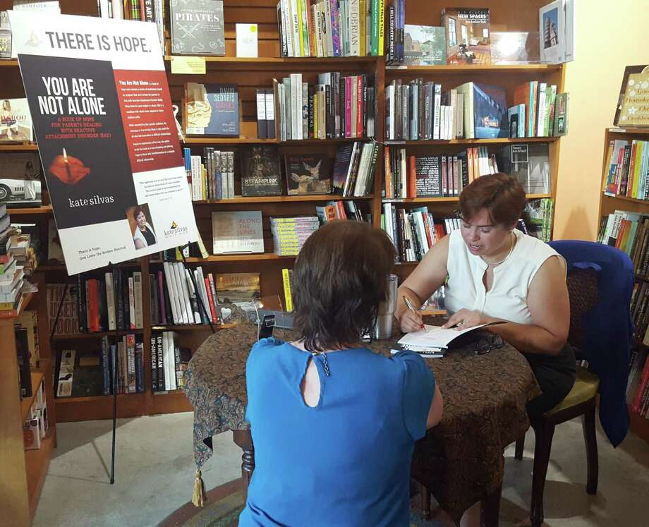 """Kate Silvas (right), signs a copy of her book, """"You Are Not Alone,"""" for Amelia Badders during her Oct. 9 book signing at The Twig Book Shop. The book's cover is on display behind the pair. Photo: Jeff B. Flinn / / NE Herald"""