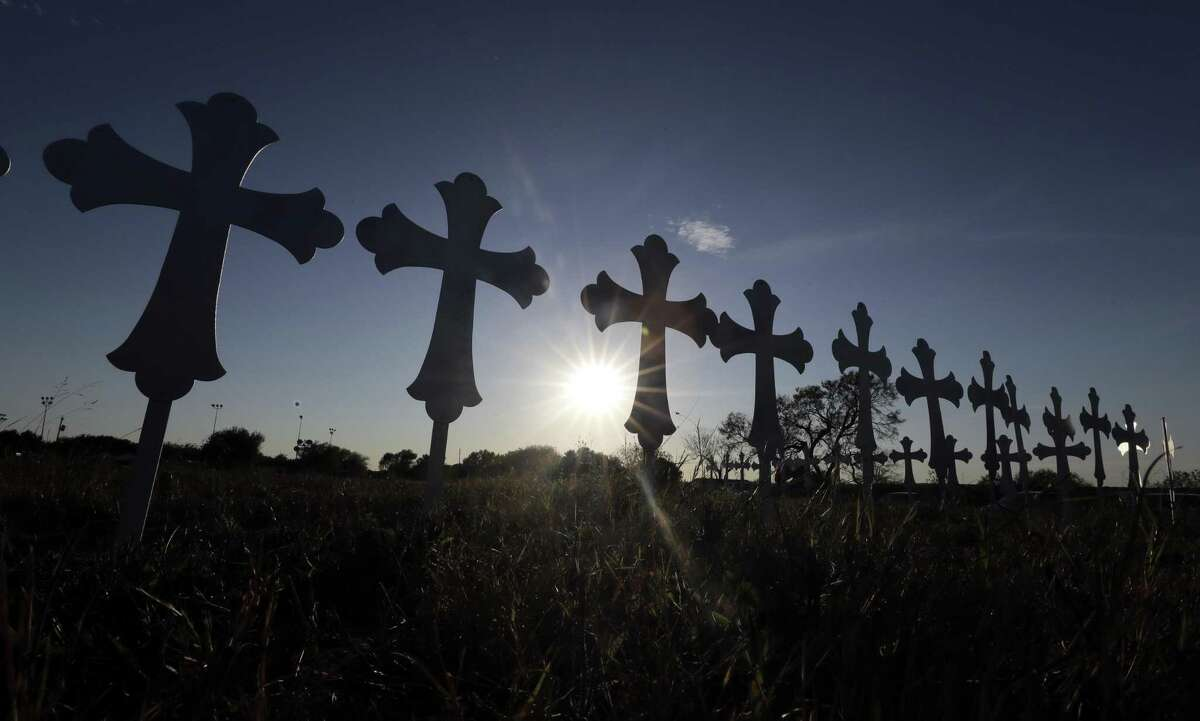 The sun sets behind 26 crosses placed in a field before a vigil for the victims of the First Baptist Church shooting Monday, Nov. 6, 2017, in Sutherland Springs, Texas.