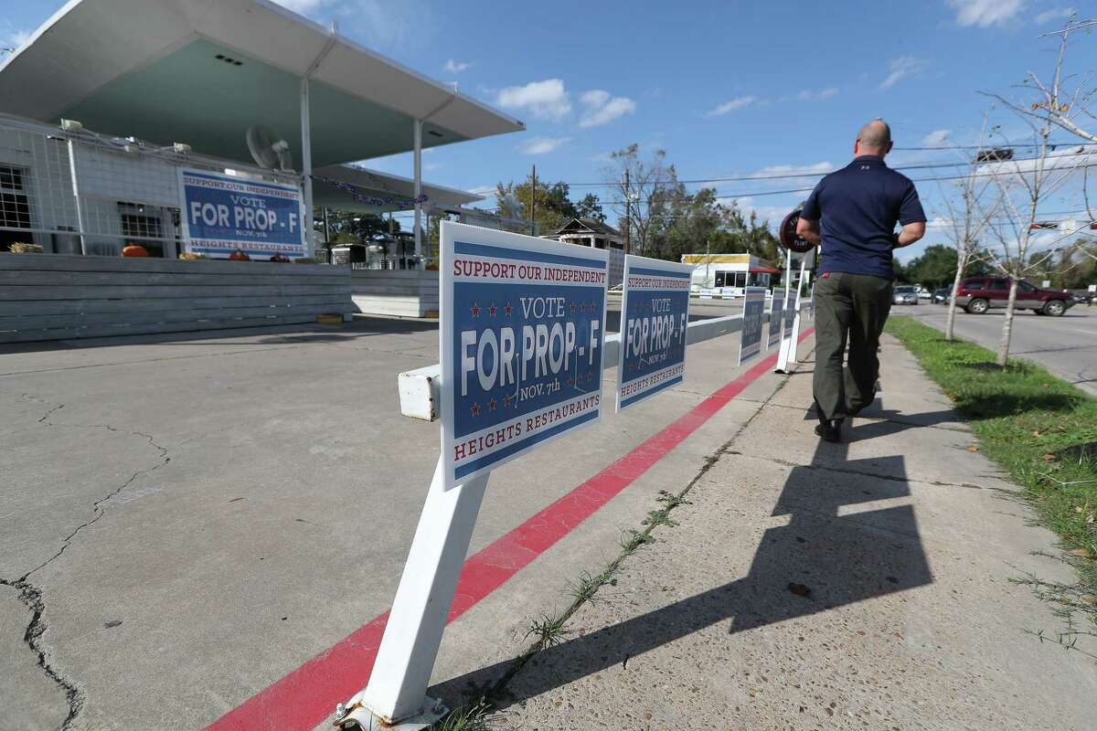 Bryan Davis walks in front of the Eight Row Flint, Yale and 11th with signs of support for Prop F Monday, Nov. 6, 2017, in Houston.