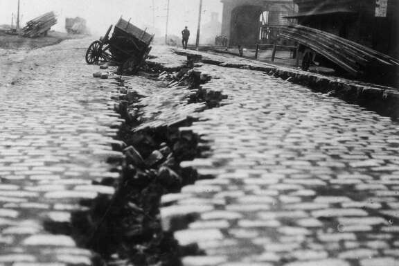 1906:  View of a cobblestone street, which was split down the middle after the Great Earthquake in San Francisco, California. A wooden cart has fallen into the crack.  (Photo by American Stock/Getty Images)