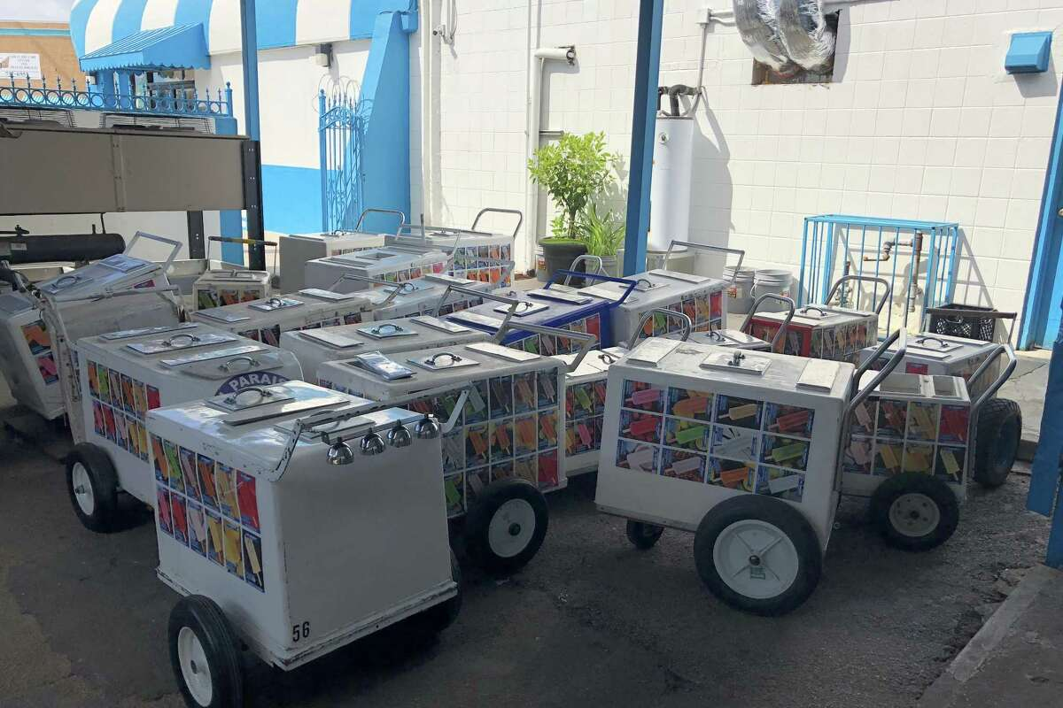 A collection of colorful paleta carts, a few with vintage bells, sits behind El Paraíso.