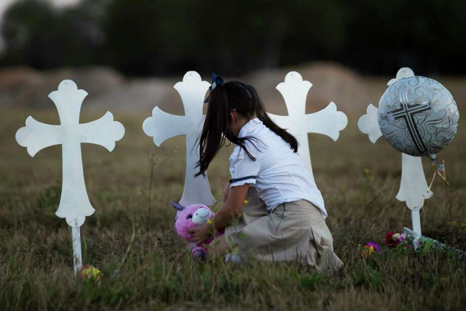 Heather Cooper, 8, leaves behind a stuffed animal by a cross representing one of the 26 lives killed during a shooting in the First Baptist Church of Sutherland Springs, Monday, Nov. 6, 2017, in Sutherland Springs. Photo: Marie D. De Jesus, Houston Chronicle / © 2017 Houston Chronicle