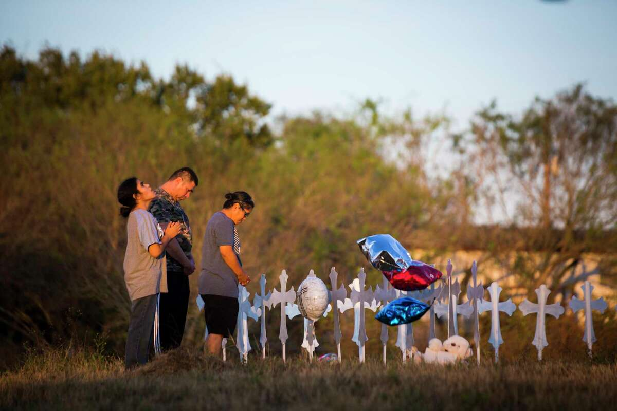Irene Hernandez, Kenneth Hernandez and Miranda Hernandez, 17, pay their respects for the victims of a shooting at a church in Sutherland Springs that took place on Sunday. Monday, Nov. 6, 2017.