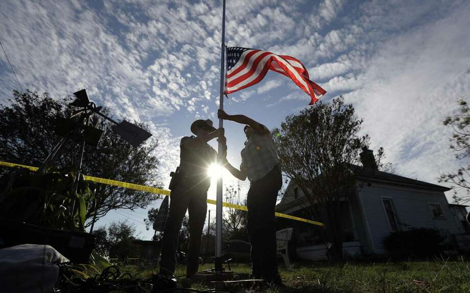 A law enforcement officer helps a man changes a flag to half-staff near the scene of a shooting at the First Baptist Church of Sutherland Springs to honor victims, Monday, Nov. 6, 2017, in Sutherland Springs, Texas. A man opened fire inside the church in the small South Texas community on Sunday, killing and wounding many. (AP Photo/Eric Gay) Photo: Eric Gay, STF / Associated Press / Copyright 2017 The Associated Press. All rights reserved.