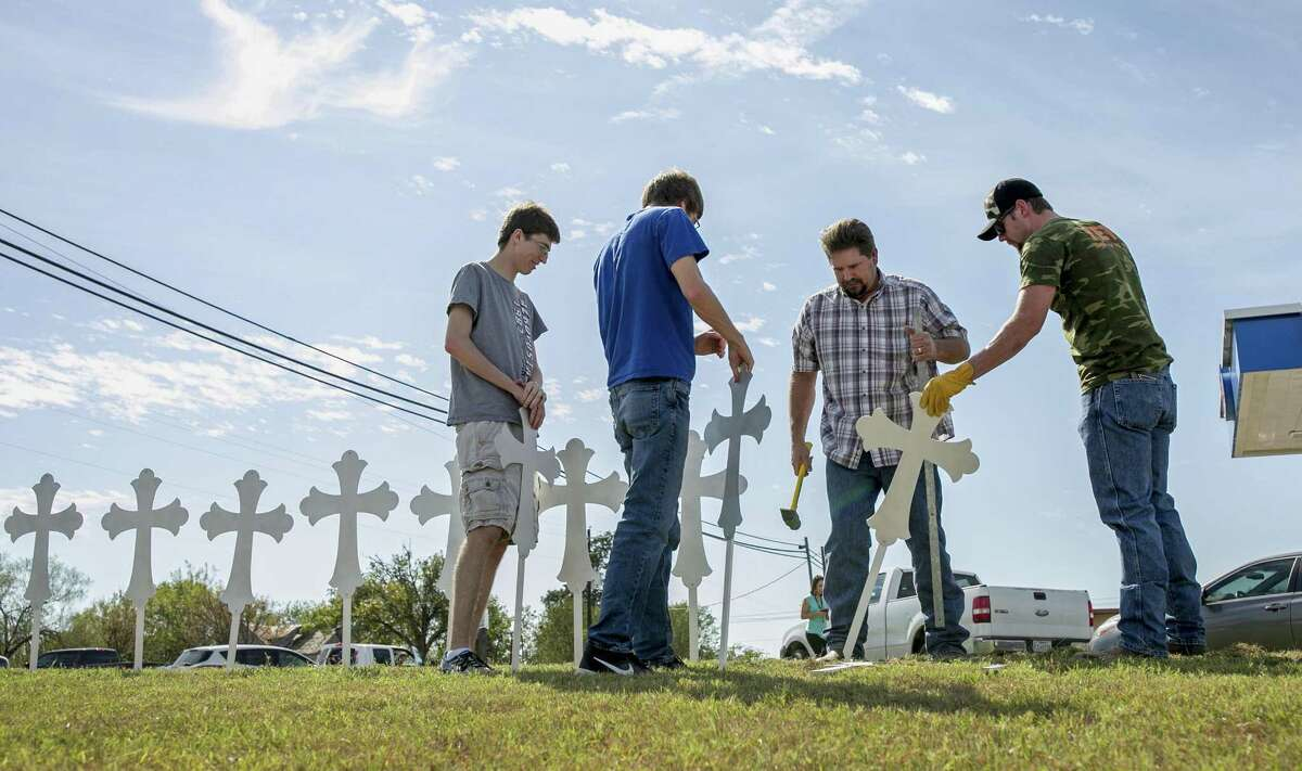 Jacob Kubena, from left, and his brother Zachary, Doug John and his son Shelby John set up a memorial of 26 metal crosses near First Baptist Church in Sutherland Springs on Monday, Nov. 6, 2017. (Jay Janner/Austin American-Statesman via AP)