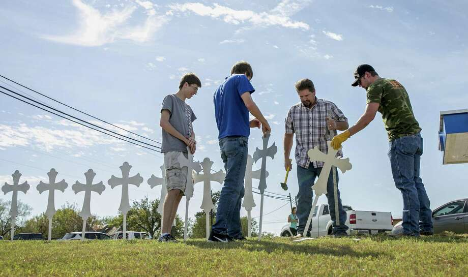 Jacob Kubena, from left, and his brother Zachary, Doug John and his son Shelby John set up a memorial of 26 metal crosses near First Baptist Church in Sutherland Springs on Monday, Nov. 6, 2017. (Jay Janner/Austin American-Statesman via AP) Photo: Jay Janner, MBO / Associated Press / Austin American-Statesman