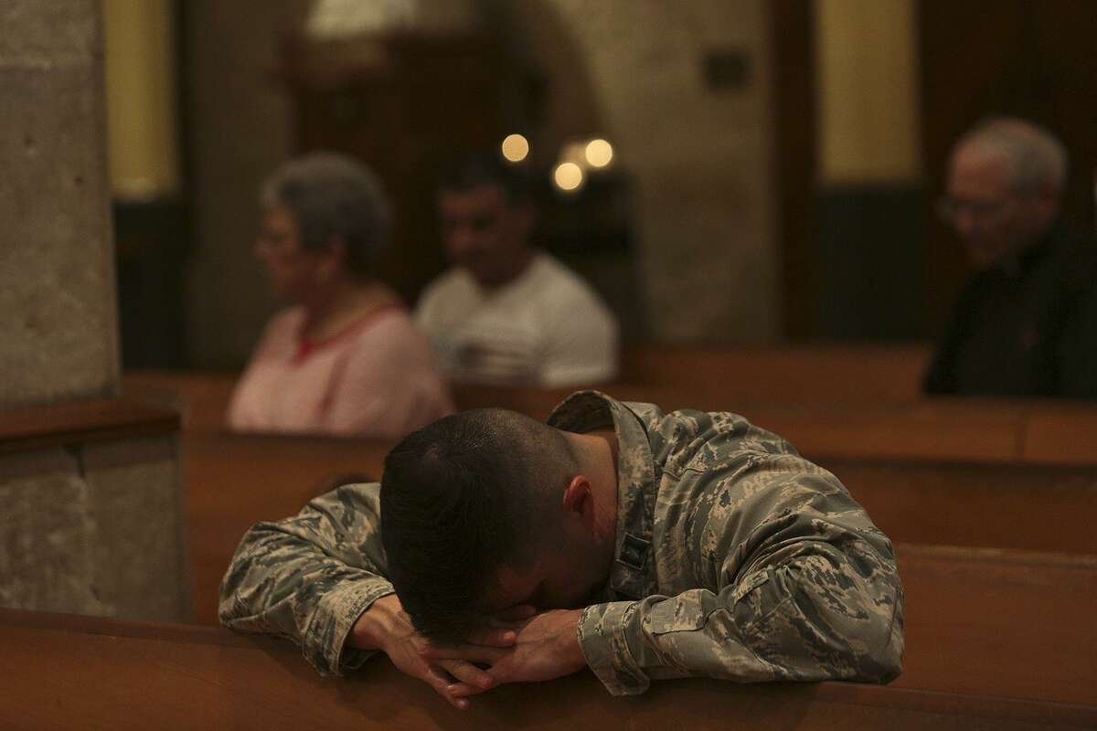 Air Force Captain Emmanuel Rivera prays during the opening Mass of the Presbyteral Convocation at San Fernando Cathedral in San Antonio on Monday, Nov. 6, 2017. Special prayers were said and a display of candles memorialized the victims of the mass shooting at First Baptist Church in Sutherland Springs during the mass.