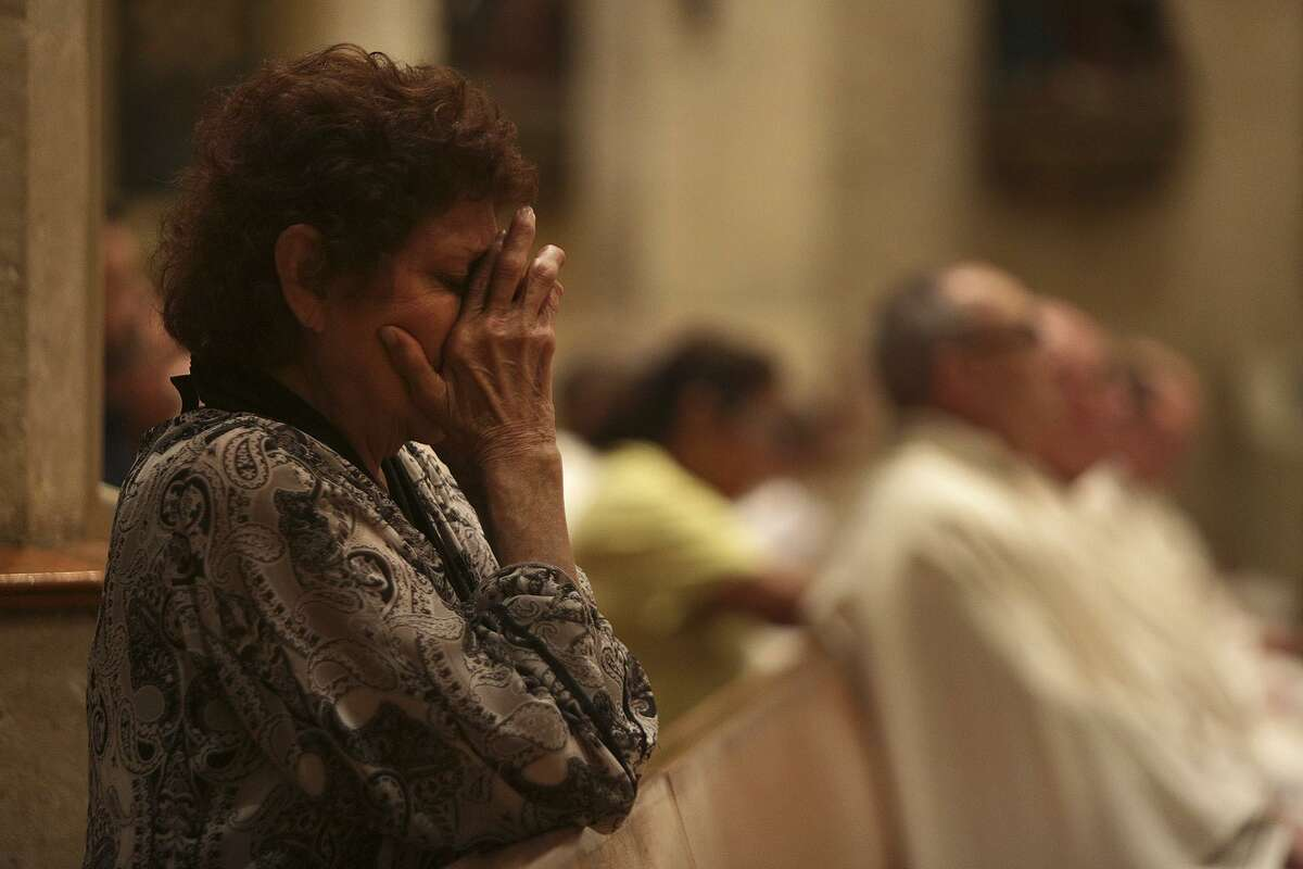 Mary Alice Robledo prays during the opening Mass of the Presbyteral Convocation at San Fernando Cathedral in San Antonio on Monday, Nov. 6, 2017. Special prayers were said and a display of candles memorialized the victims of the mass shooting at First Baptist Church in Sutherland Springs during the mass.
