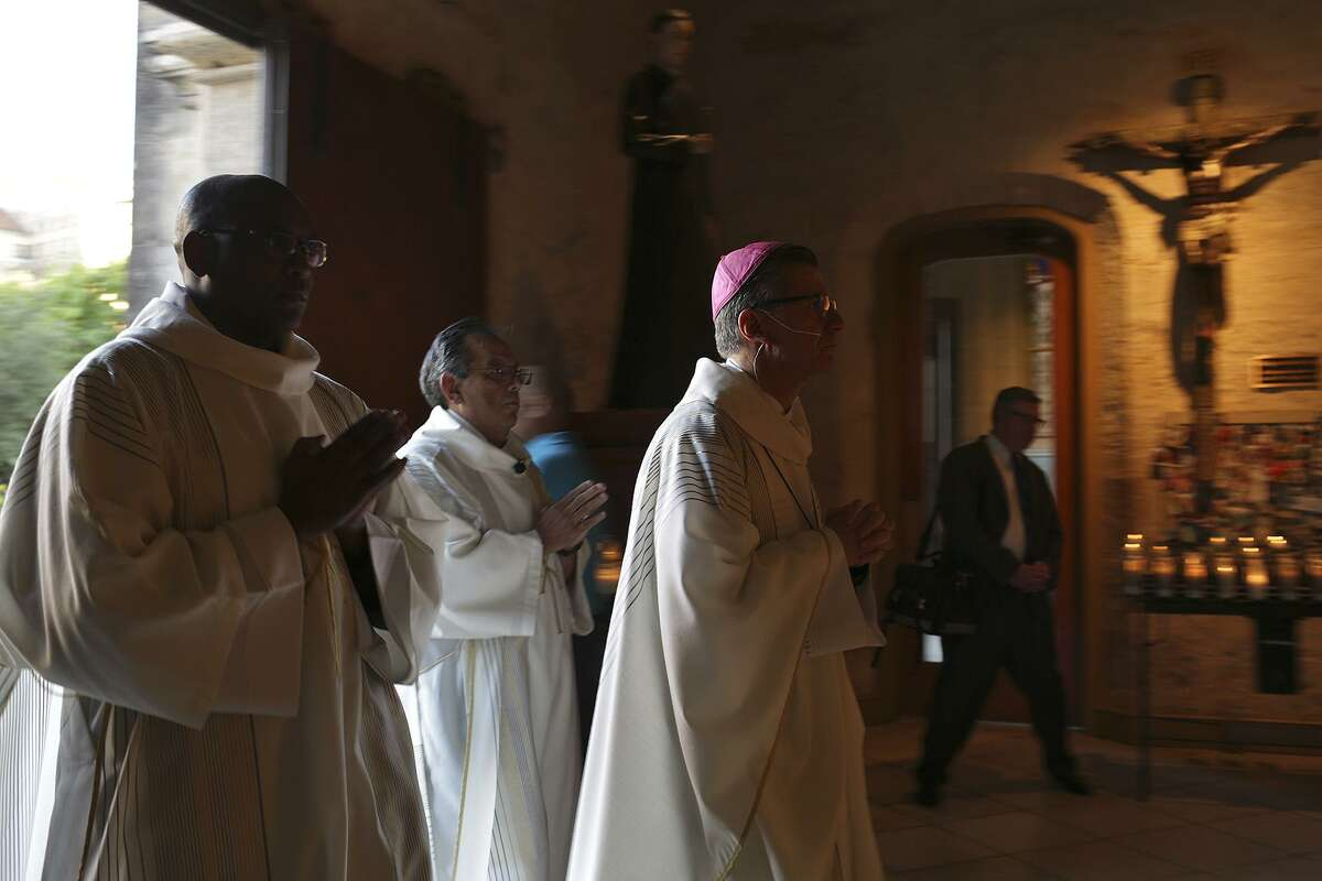 Archbishop Gustavo Garcia-Siller, center, enters San Fernando Cathedral for the opening Mass of the Presbyteral Convocation in San Antonio on Monday, Nov. 6, 2017. Special prayers were said and a display of candles memorialized the victims of the mass shooting at First Baptist Church in Sutherland Springs during the mass.