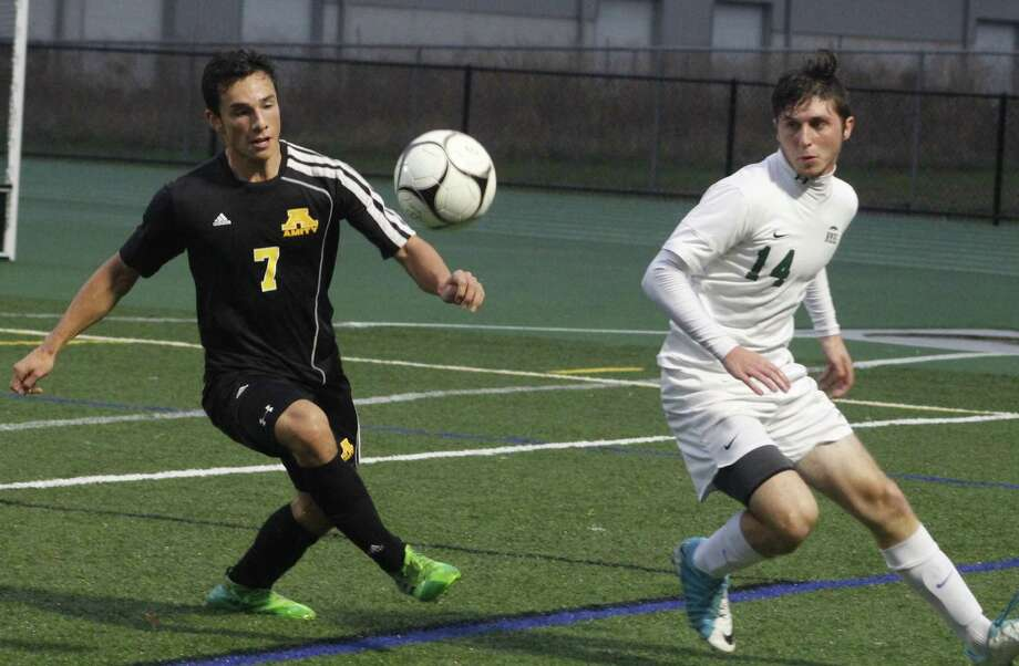 Amity's Luciano Artaza, left, and New Milford's Shane Fedigan battle for possession of the ball during the state Class LL first-round boys soccer game at New Milford High School Nov. 6, 2017. Photo: Richard Gregory / Richard Gregory
