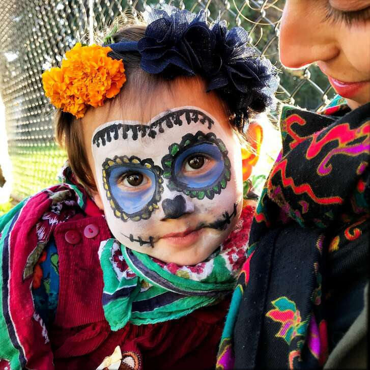 Asta Park with her mother, Camilla, as they remember Asta's father,  Joe Park, during Day of the Dead Marigold Project Festival of Altars at Garfield Square Park in San Francisco, Calif., on Thursday, November 2, 2017.