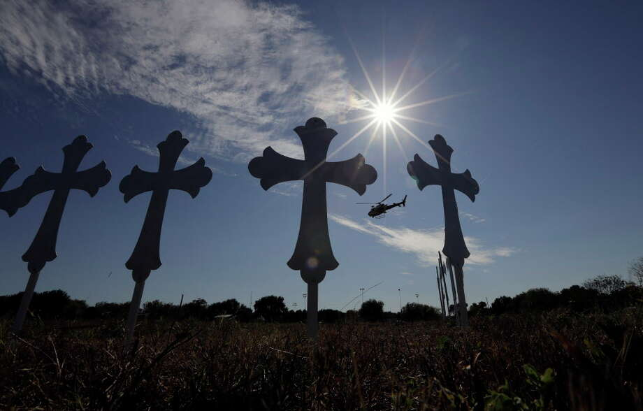 A law enforcement helicopter flies over crosses placed near the scene of a shooting at the First Baptist Church of Sutherland Springs, Monday, Nov. 6, 2017, in Sutherland Springs, Texas. A man opened fire inside the church in the small South Texas community on Sunday, killing and wounding many. (AP Photo/Eric Gay) ORG XMIT: TXEG134 Photo: Eric Gay / Copyright 2017 The Associated Press. All rights reserved.