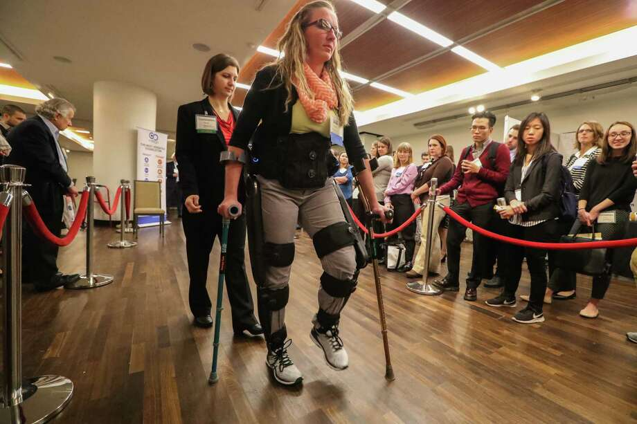 Erin Edenfield of TIRR Memorial Hermann demonstrates the Indego Exoskeletons Therapy kit with the help of Marcie Kern on Monday during the International Symposium on Wearable and Rehabilitation Robotics.  Photo: Steve Gonzales, Houston Chronicle / © 2017 Houston Chronicle