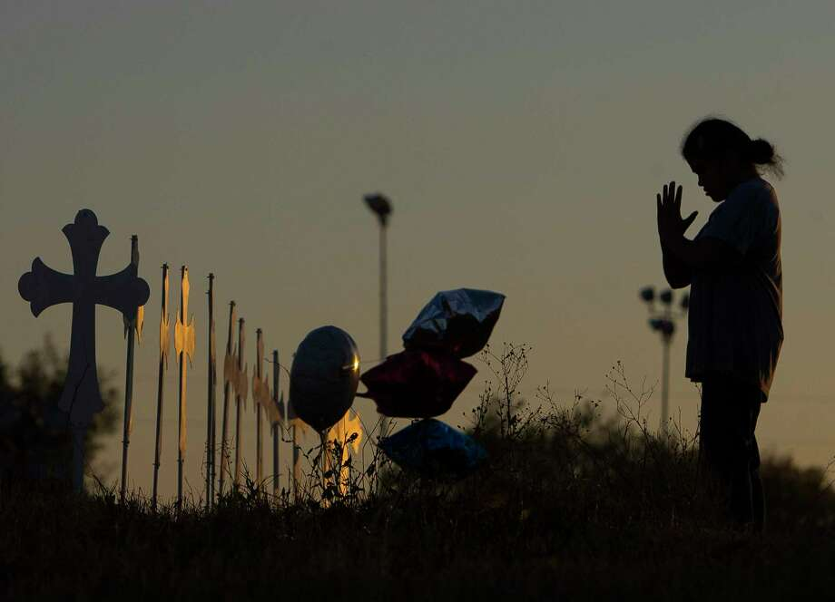 Miranda Hernandez, 17, bows her head while looking at the 26 crosses now standing in a field  in Sutherland Springs, Monday evening, Nov. 6, 2017, in Sutherland Springs. Miranda waved goodbye when leaving to a church member who used to buy her dolls when she was a child. Photo: Mark Mulligan, Houston Chronicle / © 2017 Houston Chronicle