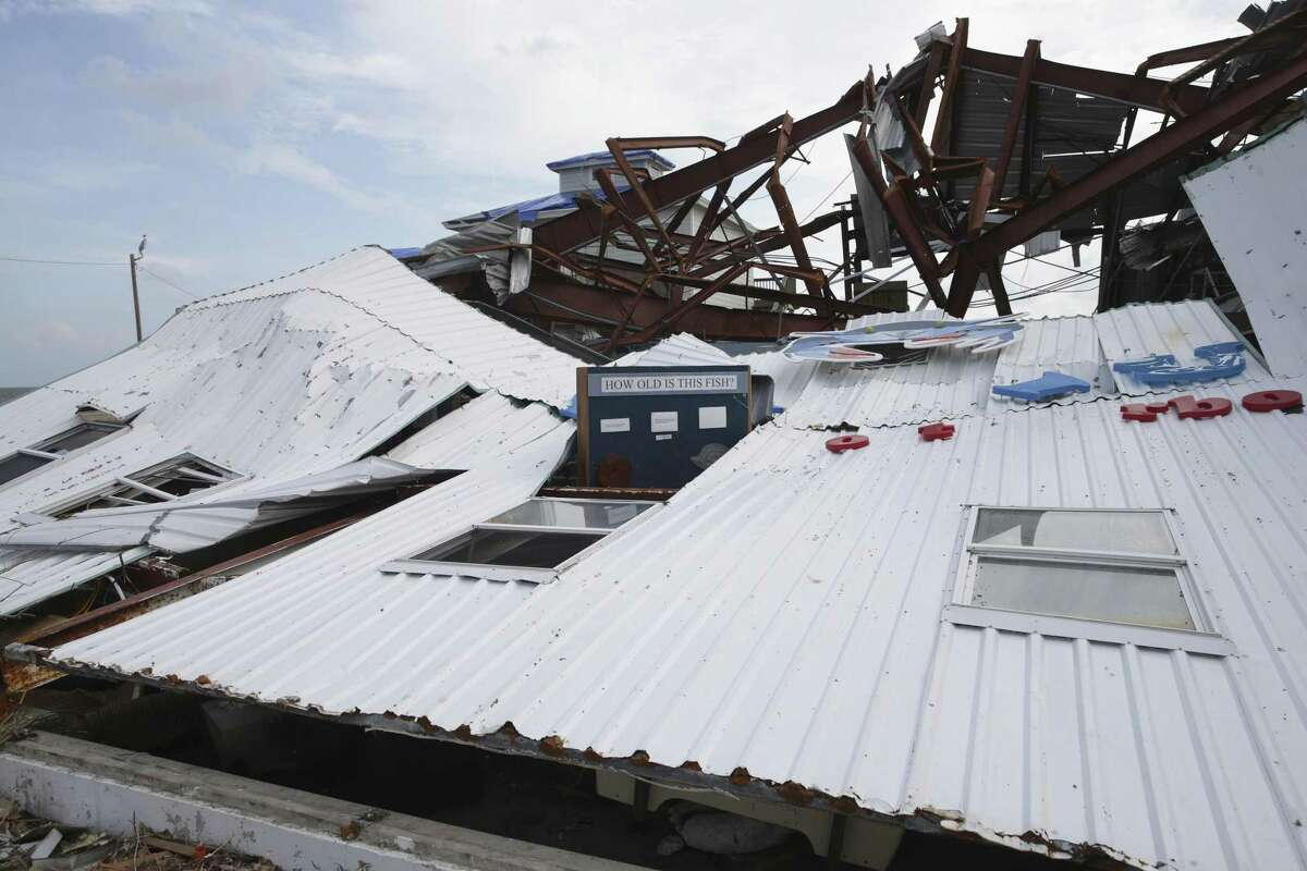"""A building on a marina lies crushed and marked """"unsafe"""" as Rockport tries to recover from Hurricane Harvy devastation. It will cost more and take longer to rebuild after Hurricane Harvey because of a construction labor shortage that is only being made worse by the nation's broken immigration policies, according to a state builders association."""