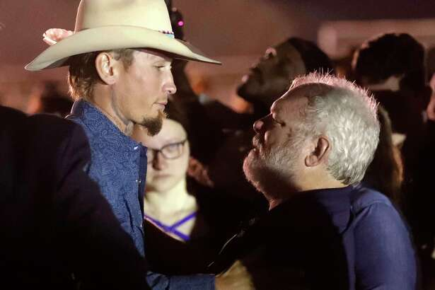 Stephen Willeford, right, hugs Johnnie Langendorff during a vigil for the victims of the First Baptist Church shooting Monday, Nov. 6, 2017, in Sutherland Springs, Texas. Willeford shot suspect Devin Patrick Kelley and Langendorff drove the truck while they chased Kelley. Kelley opened fire inside the church in the small South Texas community on Sunday, killing more than two dozen and injuring others. (AP Photo/David J. Phillip)
