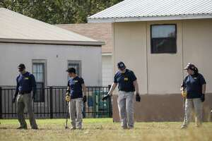 FBI personnel use metal detectors as the investigation of the mass shooting continued Monday in Sutherland Springs, Texas.