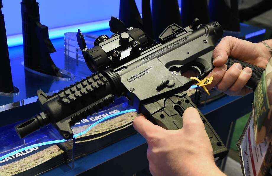 A convention attendee looks at a Mossberg International 715P semi-auto .22 LR Pistol with red dot combo at the Mossberg International booth at the 2016 National Shooting Sports Foundation's Shooting, Hunting, Outdoor Trade (SHOT) Show at the Sands Expo and Convention Center on January 19, 2016 in Las Vegas. Photo: Ethan Miller/Getty Images