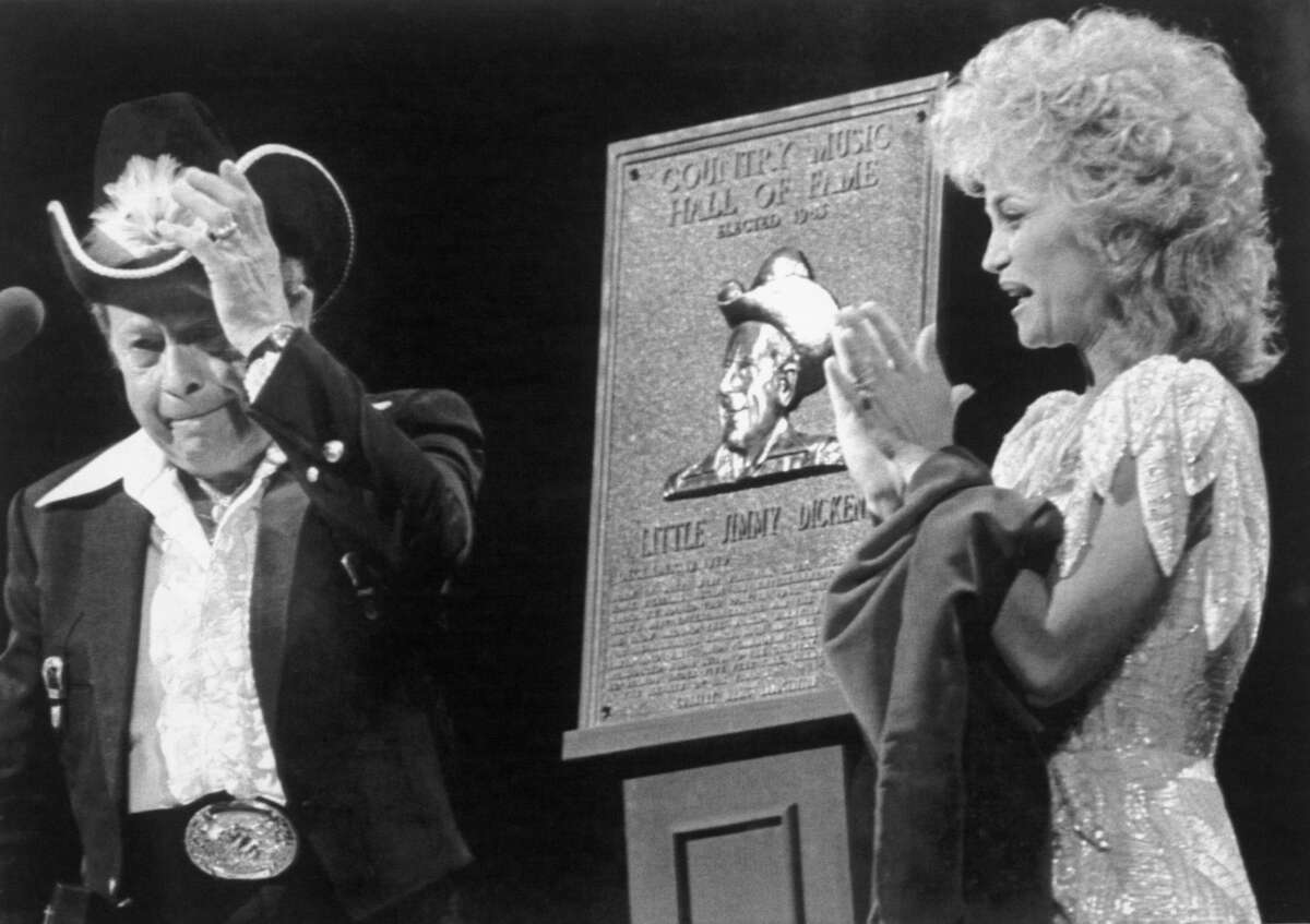 Little Jimmy Dickens tearfully steps to the microphone after he was inducted into the Country Music Hall of Fame during the 1983 Country Music Association awards presentation. At right is Barbara Mandrell who made the presentation.