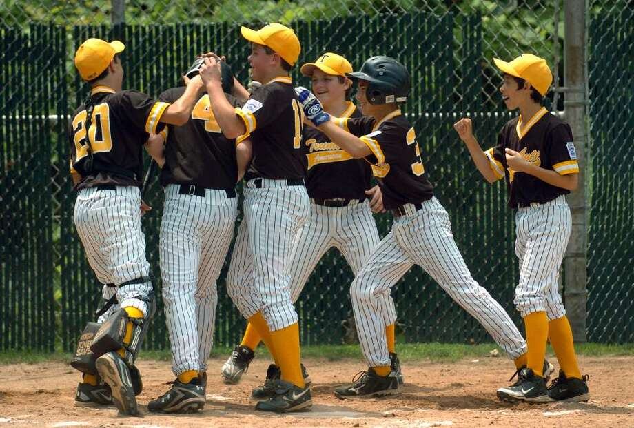 Trumbull teammates surround #4 Robert Ryan, second from left, to celebrate after he hit a homerun, during District 2 little league action at Blackham School field in Bridgeport, Conn. on Saturday June 26, 2010. Photo: Christian Abraham / Connecticut Post