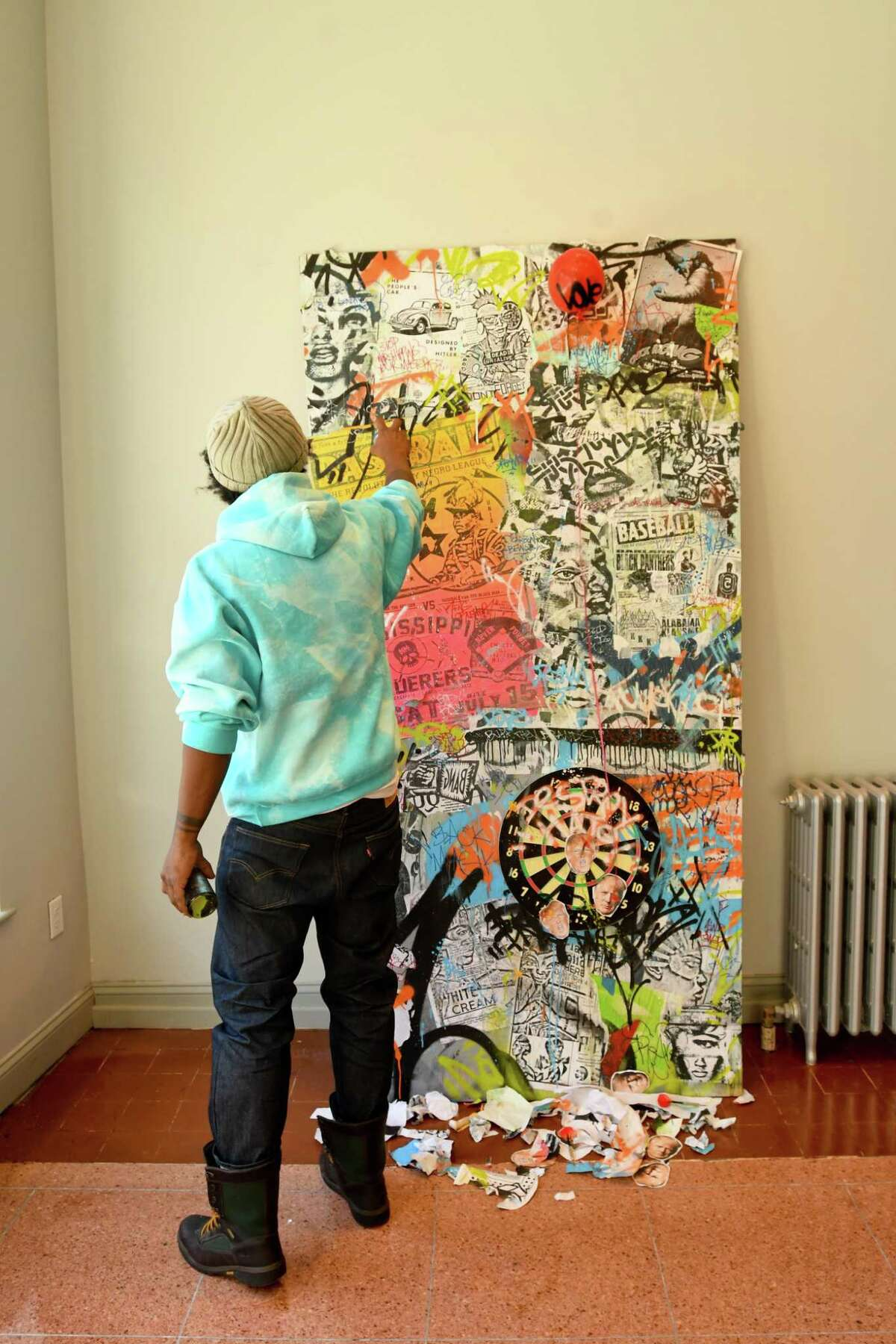Jahmane, artist and co-curator of the Blends Gallery in Bridgeport, puts the finishing touches on his artwork for the gallery's first show.