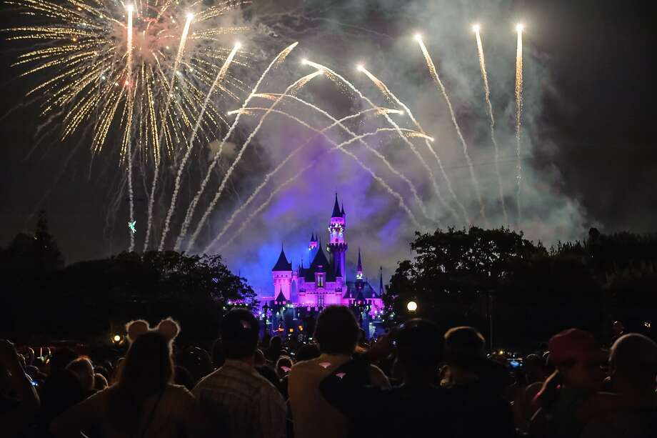 Thousands of park visitors gather on Main Street, U.S.A., for the best view of the nightly fireworks display at Disneyland. The castle lights up, changes colors and Tinker Bell (in the middle left of the photo) greets patrons as the show begins. Photo: Dino Chiecchi, San Antonio Express-News