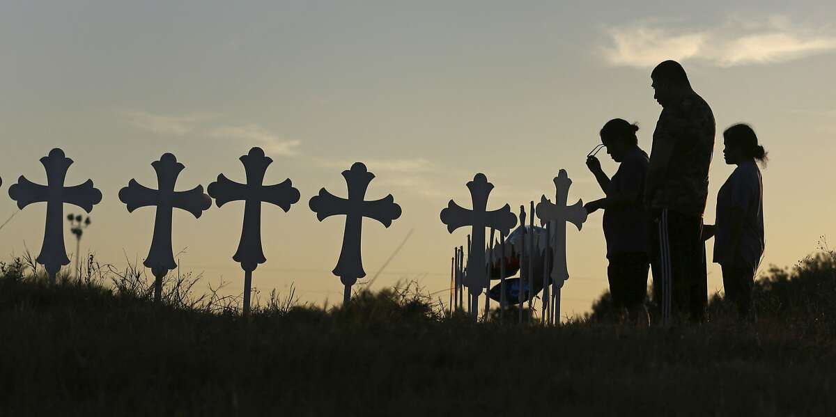 Irene and Kenneth Hernandez and their daughter Miranda Hernandez say a prayer Monday, Nov. 6, 2017, in front of some of the crosses placed in a field in Sutherland Springs, Texas, to honor those who were killed in Sunday's mass shooting when a gunman opened fire at the town's First Baptist Church. (Louis DeLuca/The Dallas Morning News)