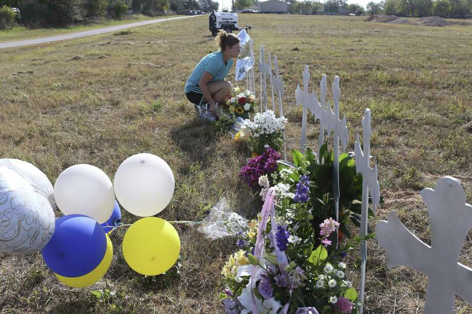 Cindy Wyatt leaves flowers Tuesday at a memorial for the First Baptist Church shooting victims in Sutherland Springs. Wyatt who is from Sutherland Springs is a member of the First Baptist Church in La Vernia which is said to have a close relationship