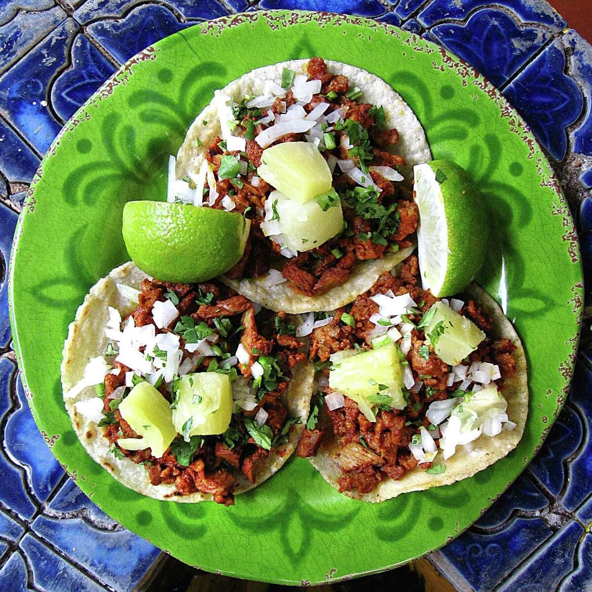 Tacos al pastor with onions, cilantro and pineapple on handmade corn tortillas from El Mirasol.