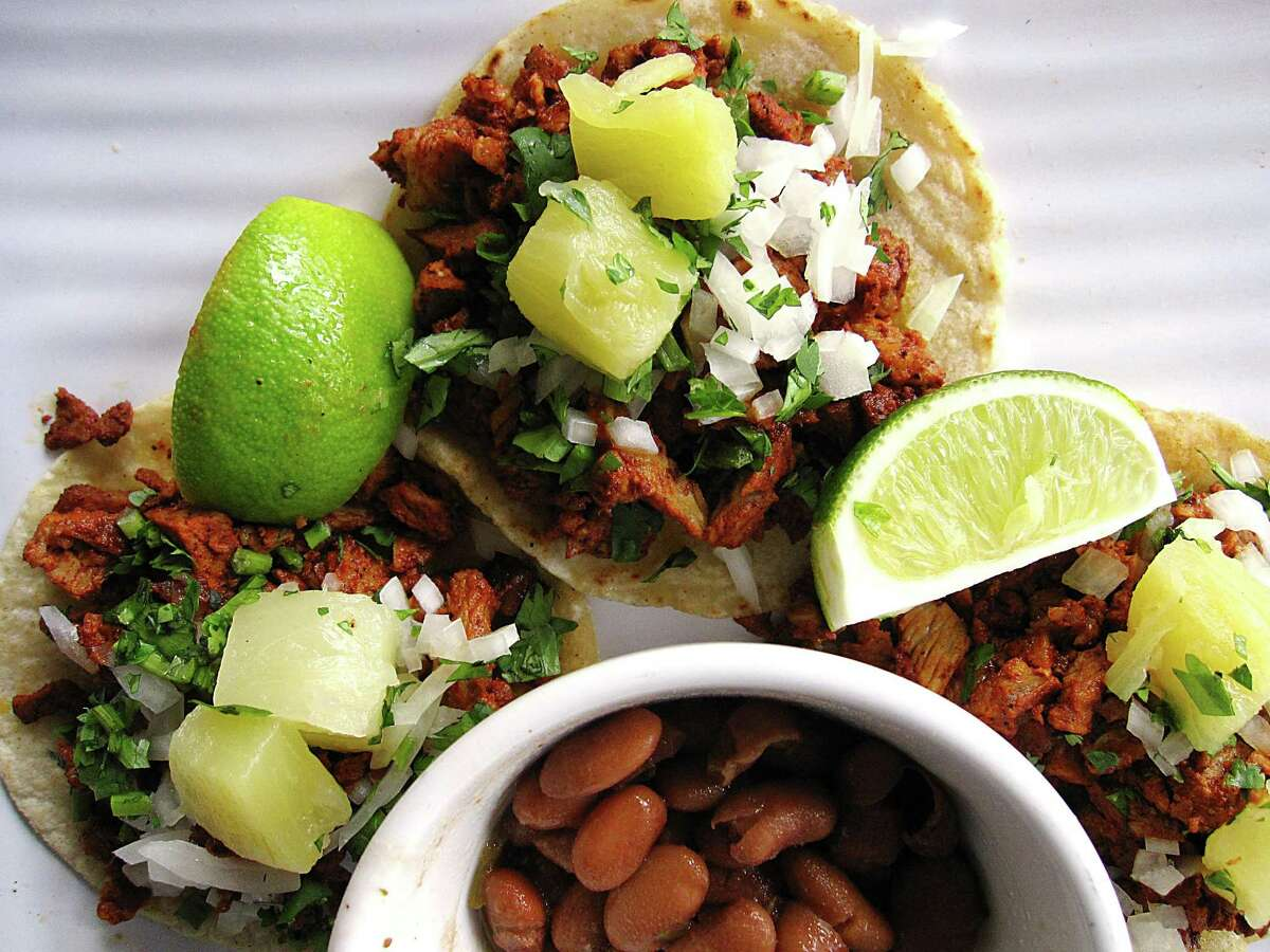 A trio of tacos al pastor on handmade corn tortillas with borracho beans from El Mirasol, which will open its new location at 938 N. Loop 1604 W. on Monday.