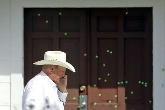 RETRANSMITTING TO ADD GREEN MARKERS ON BULLET HOLES Wilson County Sheriff Joe Tackitt Jr. walks past the front doors where bullet holes were marked by police at the First Baptist Church, Tuesday, Nov. 7, 2017, in Sutherland Springs, Texas. A man opened fire inside the church in the small South Texas community on Sunday, killing more than two dozen and injuring others. (AP Photo/David J. Phillip)