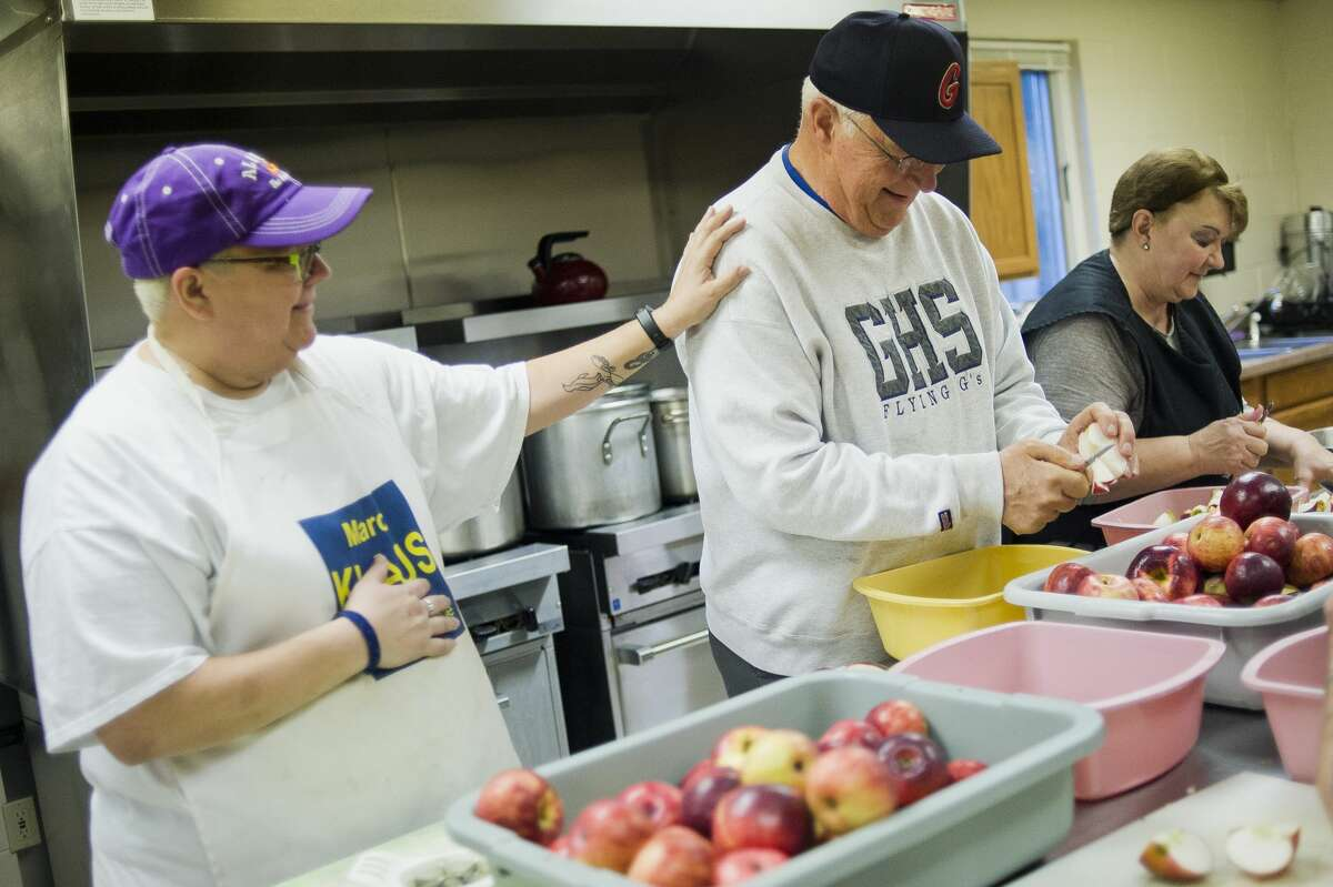 Susan Svetcos, left, jokes with Terry Brockoff, right, as they work to make applesauce on Tuesday, Nov. 7, 2017 in preparation for Our Savior Lutheran Church's annual Sausage and Sauerkraut Supper, to be held this coming Tuesday, Nov. 14. A team of about 20 volunteers got together at the church to core, slice, cook and mash bushels of Cortland apples to make 40 gallons of applesauce for the feast. (Katy Kildee/kkildee@mdn.net)