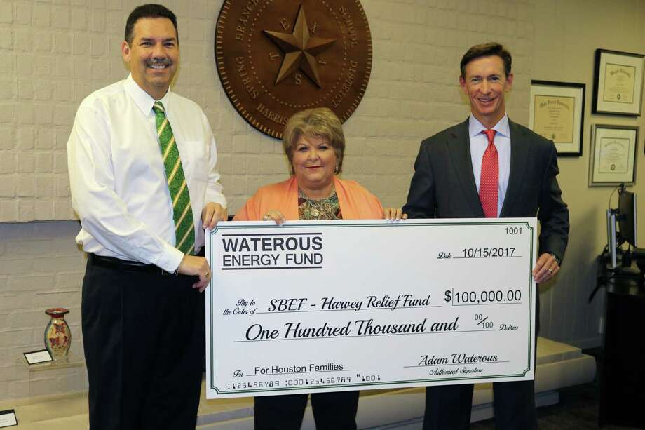Memorial resident, Spring Branch ISD parent and Waterous Energy Fund Managing Director Michael Buckingham presents a check for $100,00 to Spring Branch ISD Superintendent Scott Muri and Spring Branch Education Foundation Executive Director Cece Thompson for the SBEF Harvey Relief Fund. Photo: Courtesy Photo