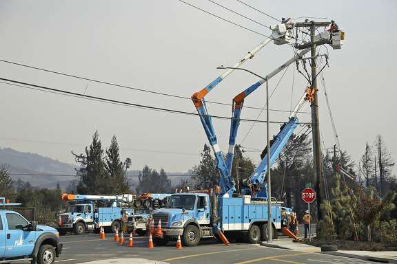FILE - In this Oct. 11, 2017 file photo, a Pacific Gas & Electric crew works at restoring power along the Old Redwood Highway in Santa Rosa, Calif. A report says California utilities have delayed efforts for nearly a decade to map where power lines pose the greatest wildfire risk. The report Sunday, Oct. 22, in The Mercury News comes as the state investigates whether downed power lines owned by Pacific Gas & Electric Co. sparked the deadliest wildfires in California history. (AP Photo/Eric Risberg, File)