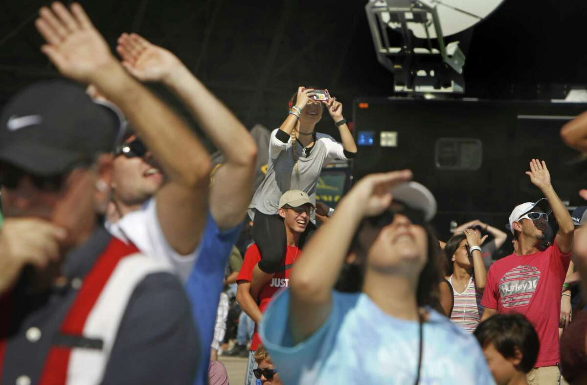 """Crowds watch as an F-35 jet and a P-51 plane fly over during the air show, whose theme was """"Your History, Our Legacy."""""""