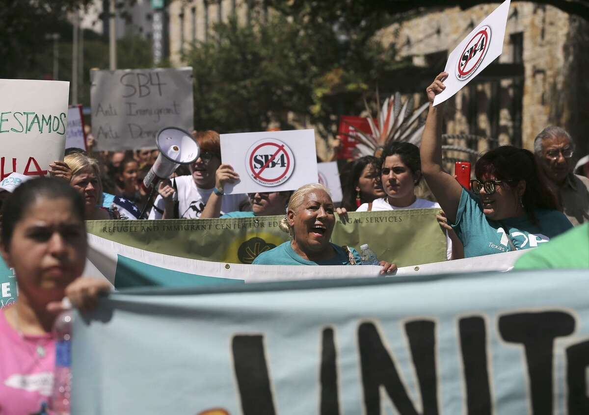 """Protesters chant Friday September 1, 2017 during a march in downtown San Antonio against Senate Bill 4. A federal judge halted most of Texas?' ban on sanctuary cities Wednesday ?- two days before the law was to take effect. In his ruling, U.S. District Judge Orlando Garcia halted penalties for officials who endorse policies in violation of Senate Bill 4, saying it likely violates the First Amendment. SB 4 allows the attorney general to fine or remove from office local officials who ?""""adopt, enforce, or endorse a policy under which the entity or department prohibits or materially limits the enforcement of immigration laws.?"""" The law also creates penalties for local officials who block police from asking about immigration status."""