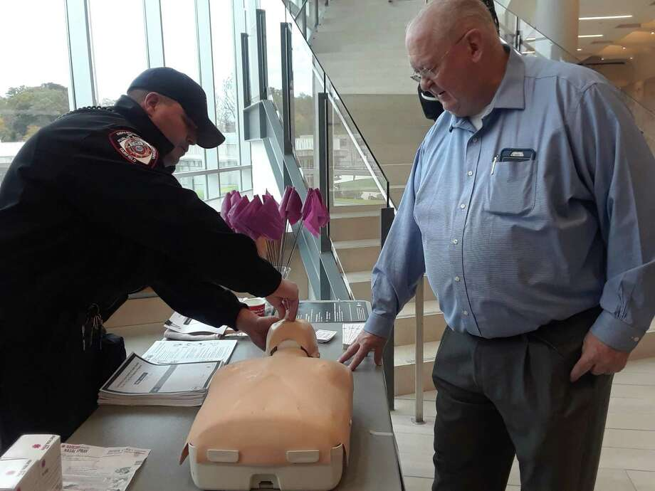 """Officer Patrick Cleary, with the Fairfield University campus police, (left) shows Michael Doody, Fairfield U. director of restorative mentoring, how to administerNarcan, the nasal spray used to counteract the impact of a drug overdose. The training was part of Fairfield U.'s """"Overdose Awareness and Prevention Day,"""" which took place Tuesday, Nov. 7, 2017, on the university's campus. Photo: Amanda Cuda / Hearst Connecticut Media"""